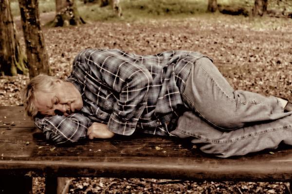 Homme dormant dehors sur un banc